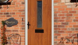Composite entrance door in oak colour finish and black traditional hardware